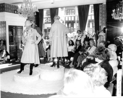 Models wearing rain macs and knee high boots at a fashion show for Dickins and Jones, c.1960s.