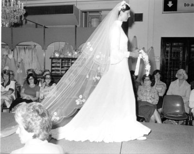 Models wearing bridal gown on the catwalk at a fashion show for Dickins and Jones, c.1960s.